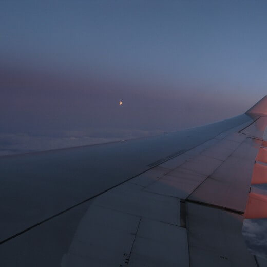 An airplane wing and the moon at sunset