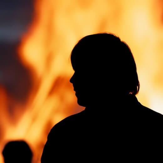 A man looking at a bonfire
